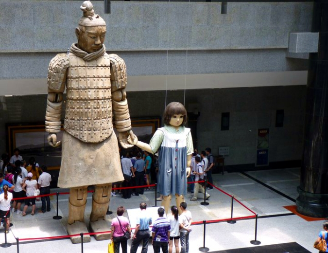 Picture of a huge, puppet terracotta warrior holding the hand of a little girl puppet