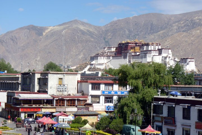 Picture of rooftop view at Jokhang Temple with Potala Palace in background, taken in Lhasa, Tibet