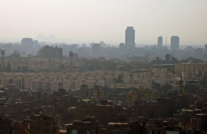 Picture of polluted Cairo skyline with pyramids visible in background