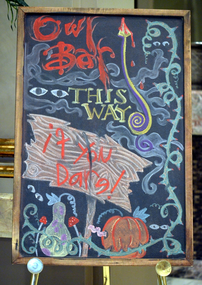 Picture of A Halloween-themed chalkboard in the Belvedere's lobby beckons thirsty customers to the bar